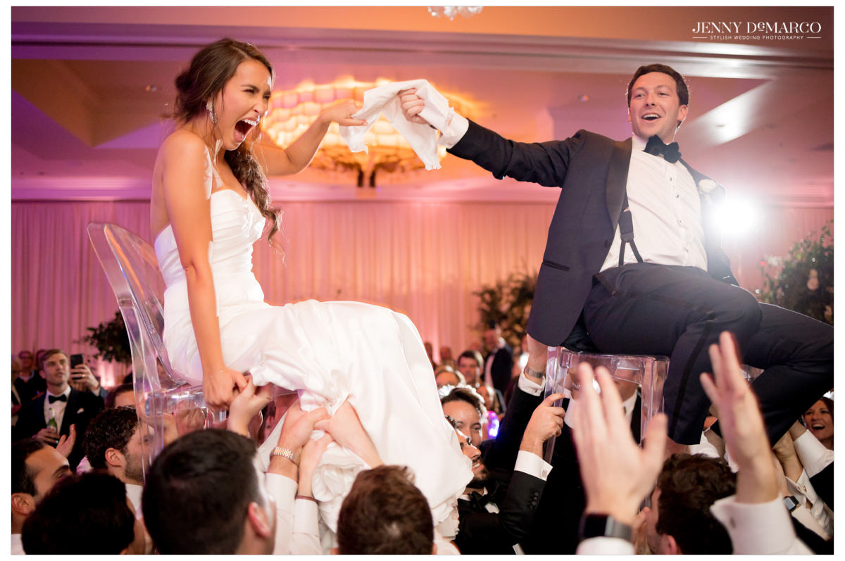 The couple celebrates with the Jewish chair tradition.