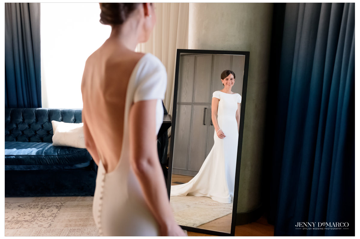 Bride wears a white satin fitted wedding gown.