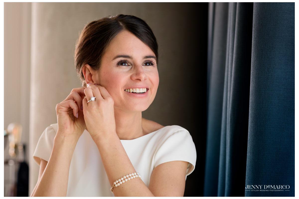 Bride puts on earrings.