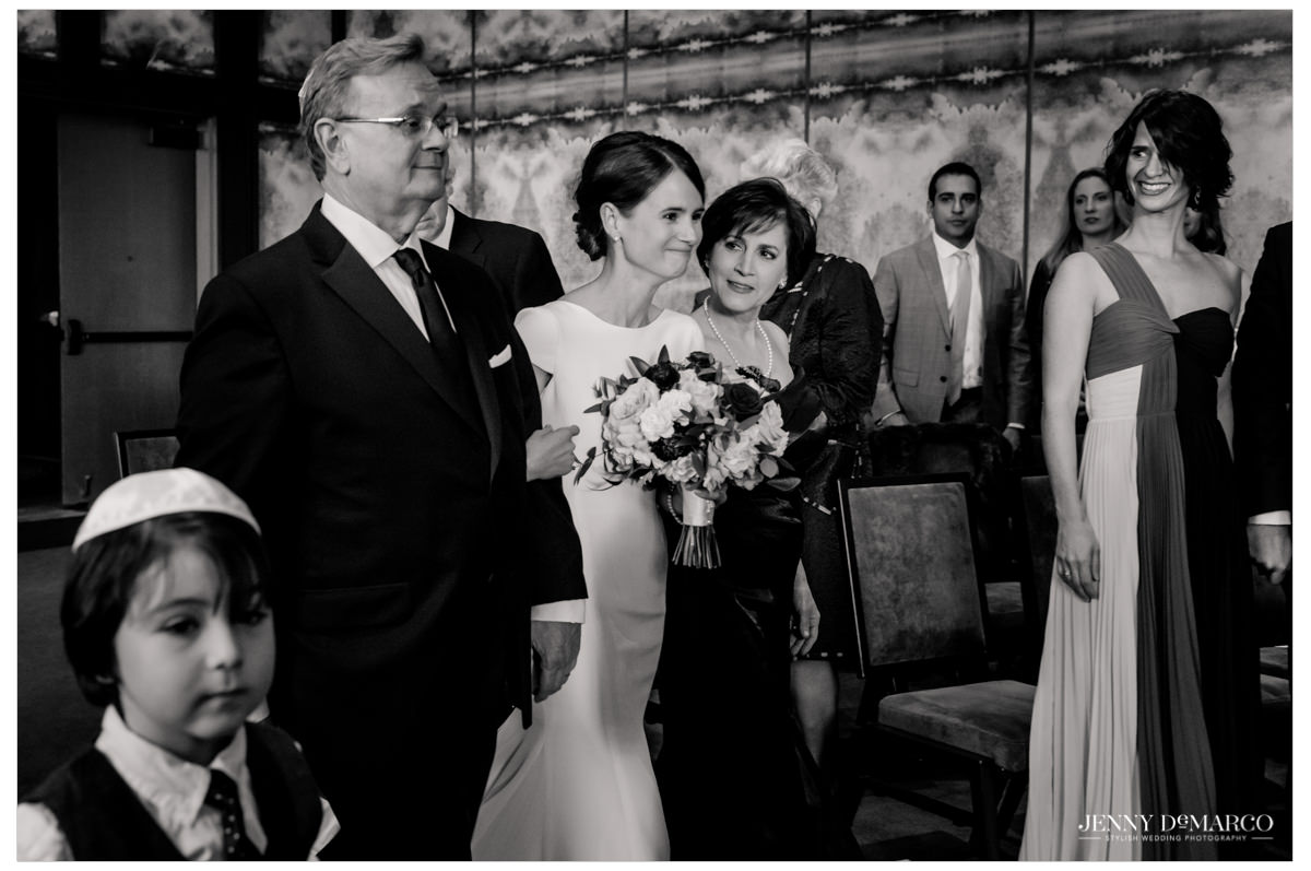 Bride is walked down the aisle by her parents.