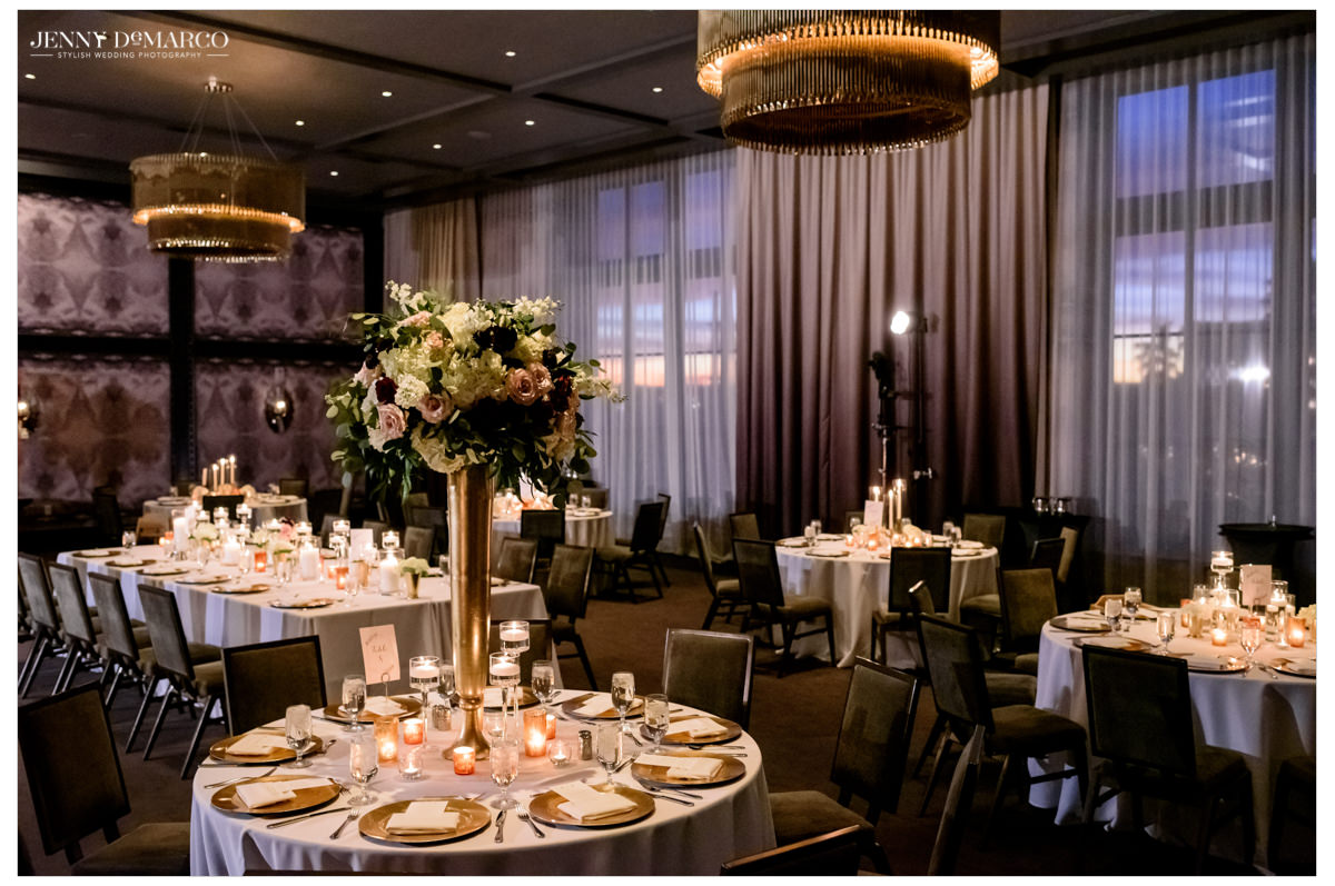 Wedding reception is decorated with green and white florals and round table.