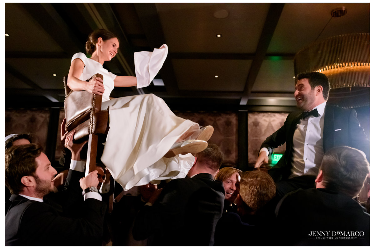 The couple is raised in chairs as part of the Jewish tradition.