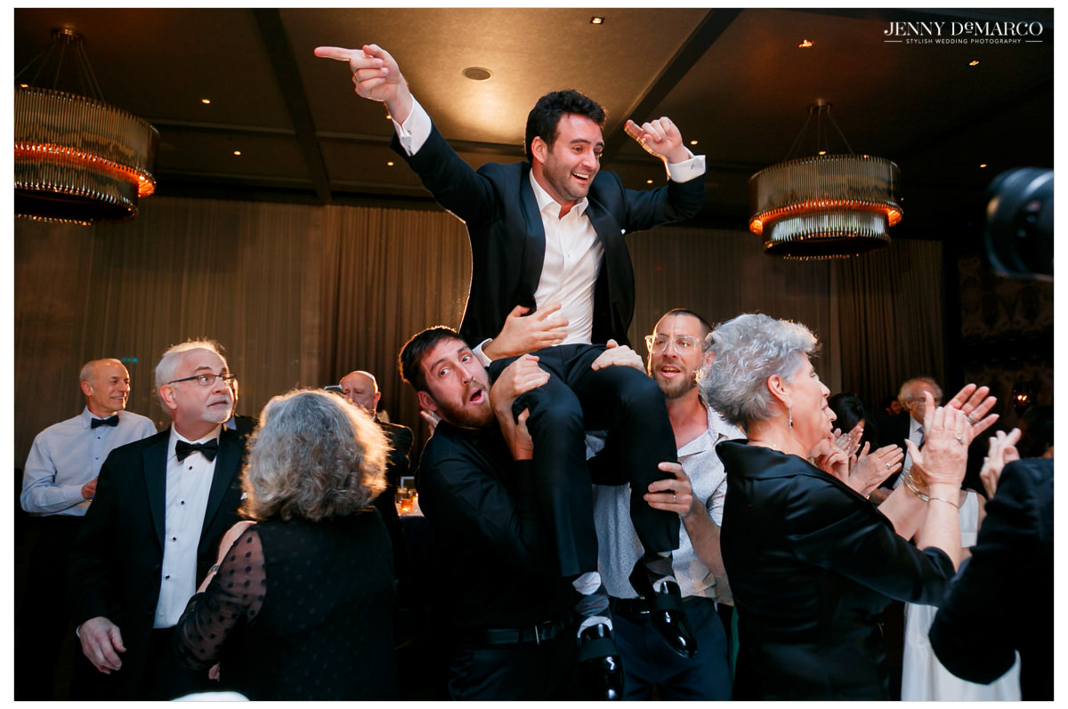 Groom is lifted in the air by his friends.