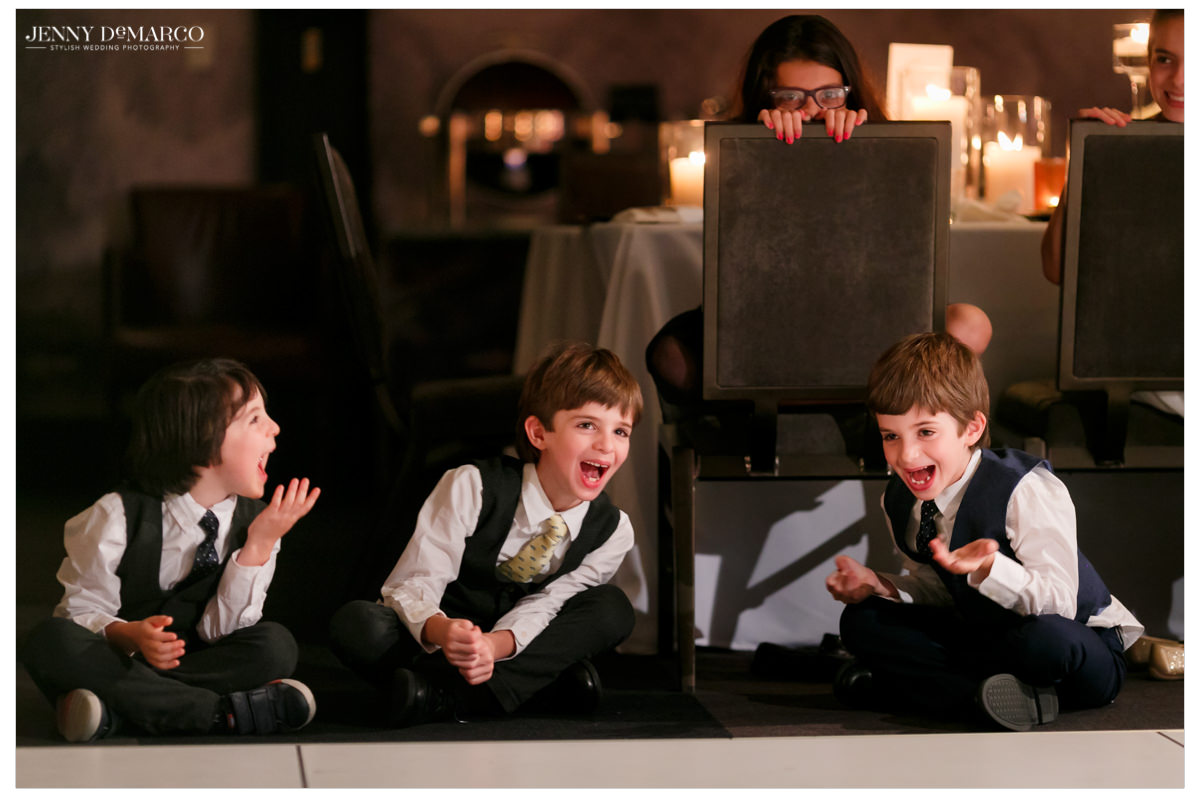 Little boys laugh as they watch the guests.