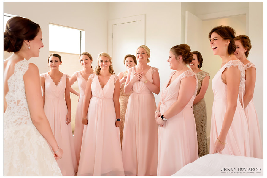 Bridesmaids reacting to seeing the bride in her wedding dress