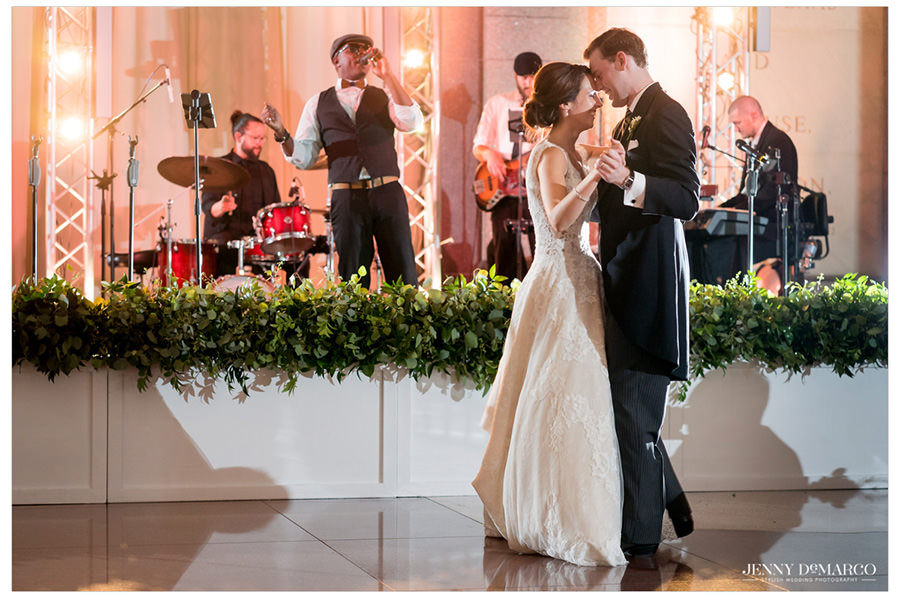 Bride and groom sharing their first dance with band in the background