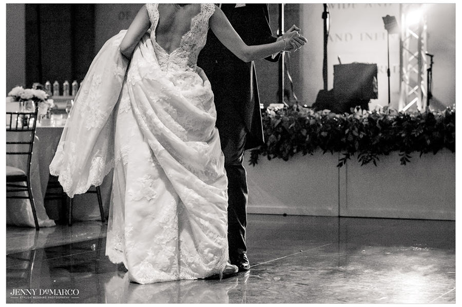 Bride holding up her dress during the first dance with her new husband