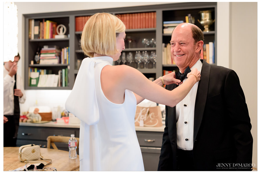 Bride adjusts the bow-tie around her father's neck as they smile at each other in excitement.