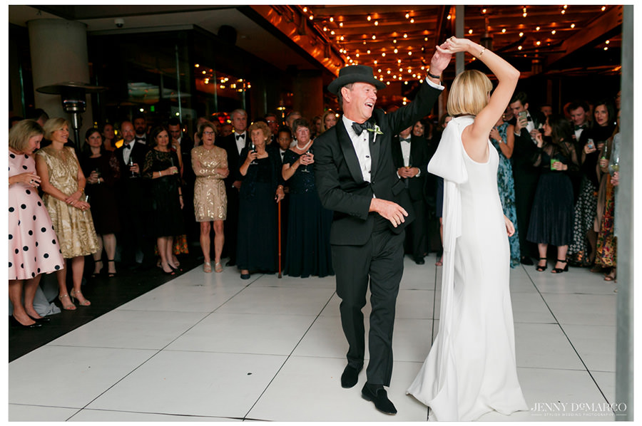Bride does a twirl with her father on the dance floor during the father-daughter dance.