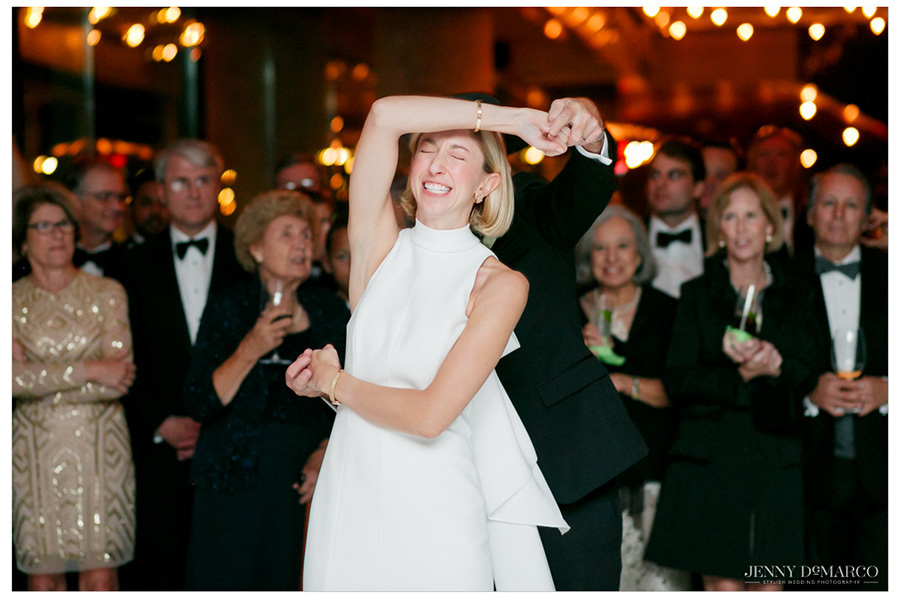 The bride scrunches up her face in laughter as she is twirled on the dance floor of her reception.