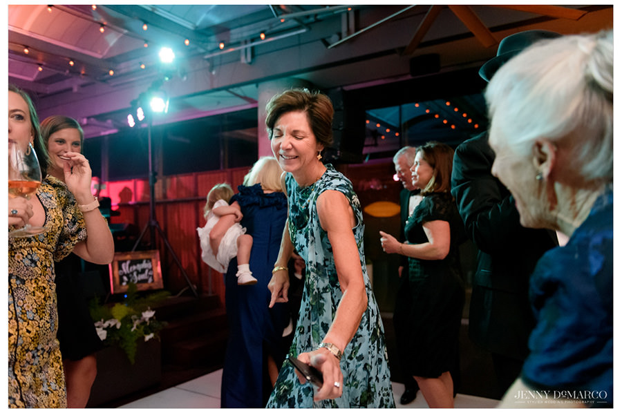 Woman in green floral dress dances and laughs at herself on the dance floor during the reception.