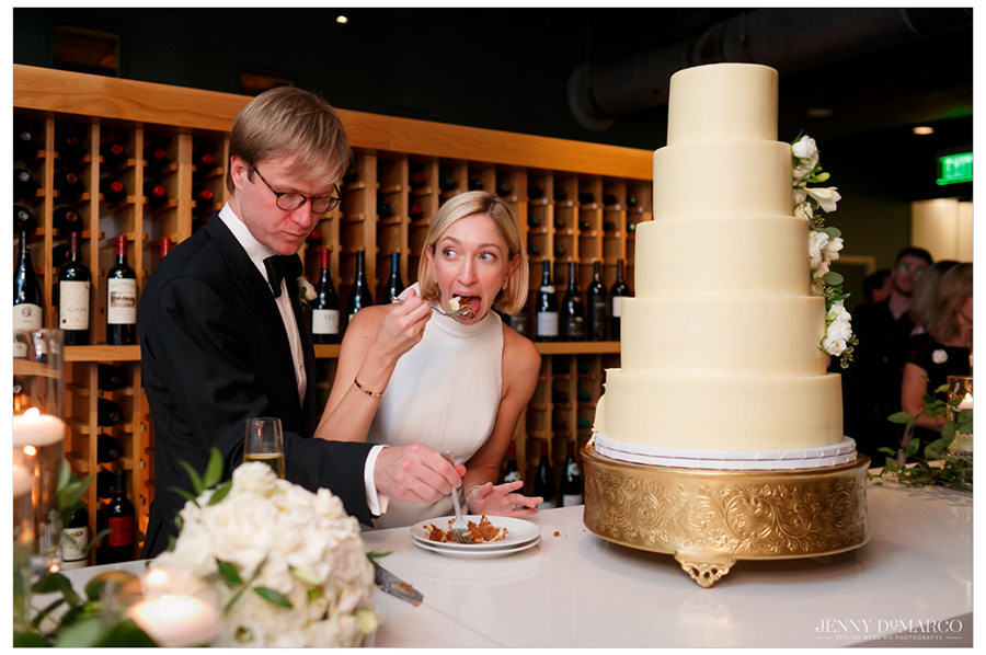 Bride and groom share their first slice of their five-tier cream wedding cake.