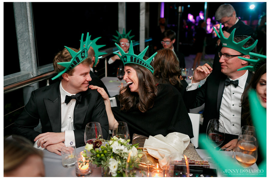 Friends of the bride and groom laugh in their Statue of Liberty caps while eating during the reception.