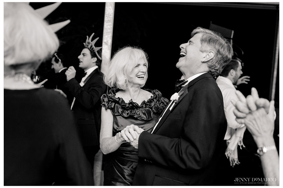 Parents of the groom laugh in each other's arms on the dance floor of the reception.