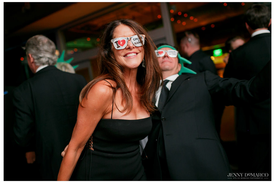 Friends of the bride and groom smile towards the camera as they dance at the reception with their customizes sunglasses.