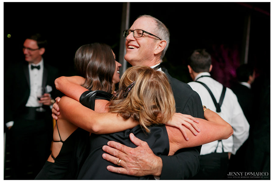 Family members laugh and embrace each other with huge grins during the reception.