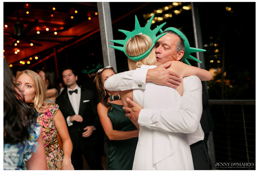 Bride hugs her guests goodbye after the reception wearing their New York caps.