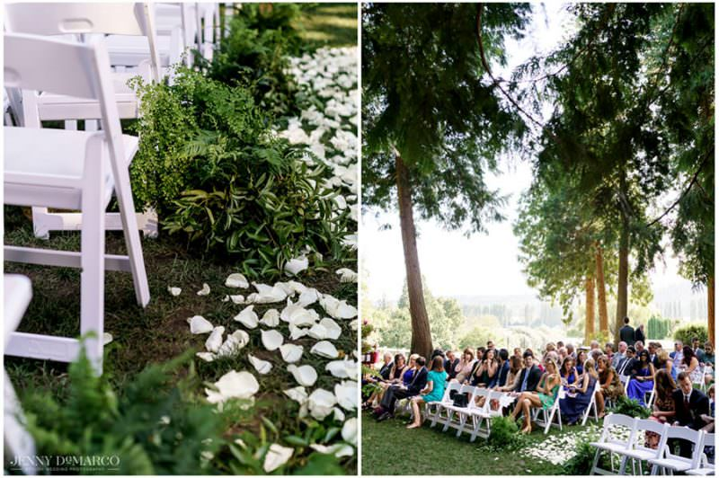 rose petals coating the aisle and wedding guests in their seat in the forest