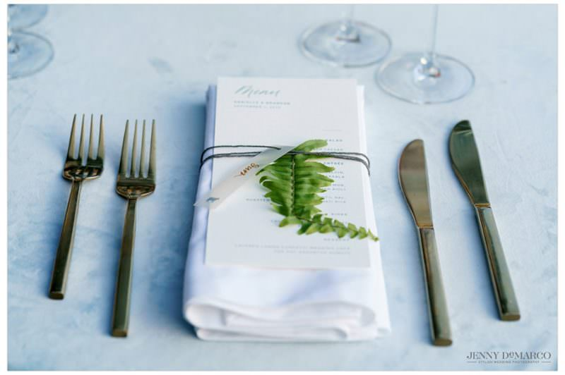place setting at the wedding reception with a fern leaf