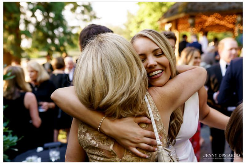 bride smiling while hugging a wedding guest