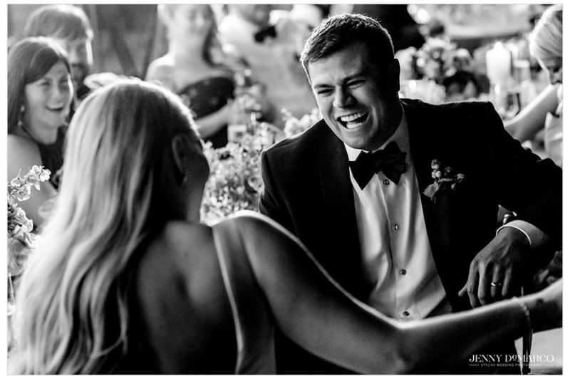 groom and bride laughing at speeches during the wedding reception
