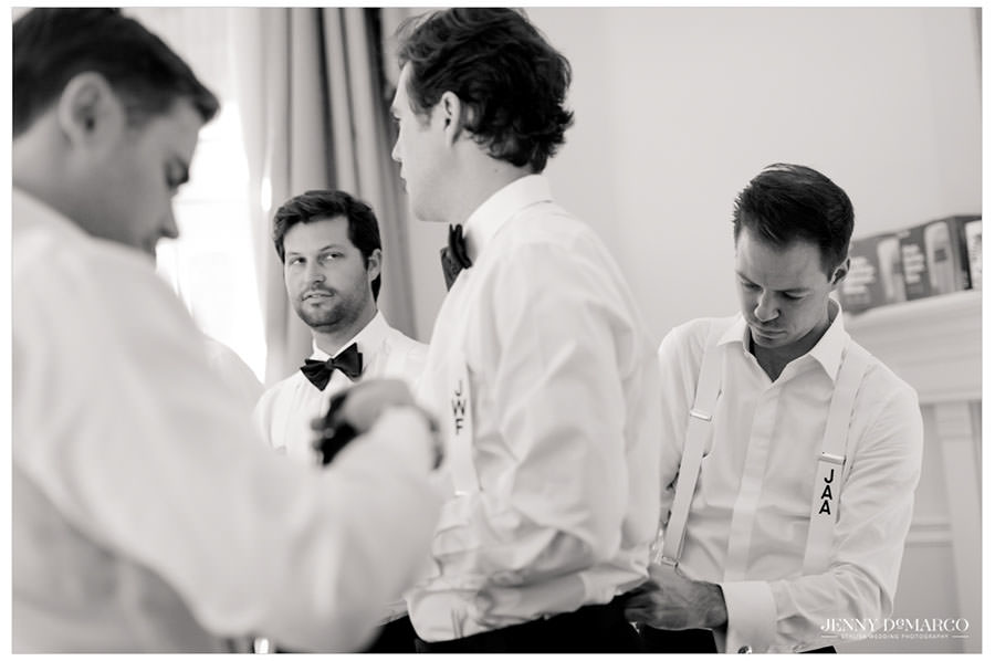 Groomsmen helping each other get ready. Suspenders!