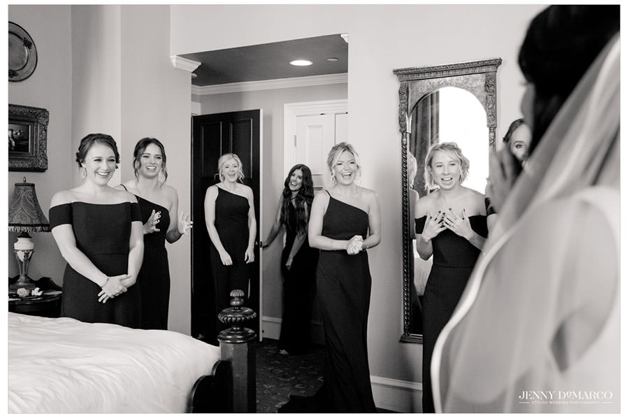 Bride showing her bridesmaids her in her wedding dress