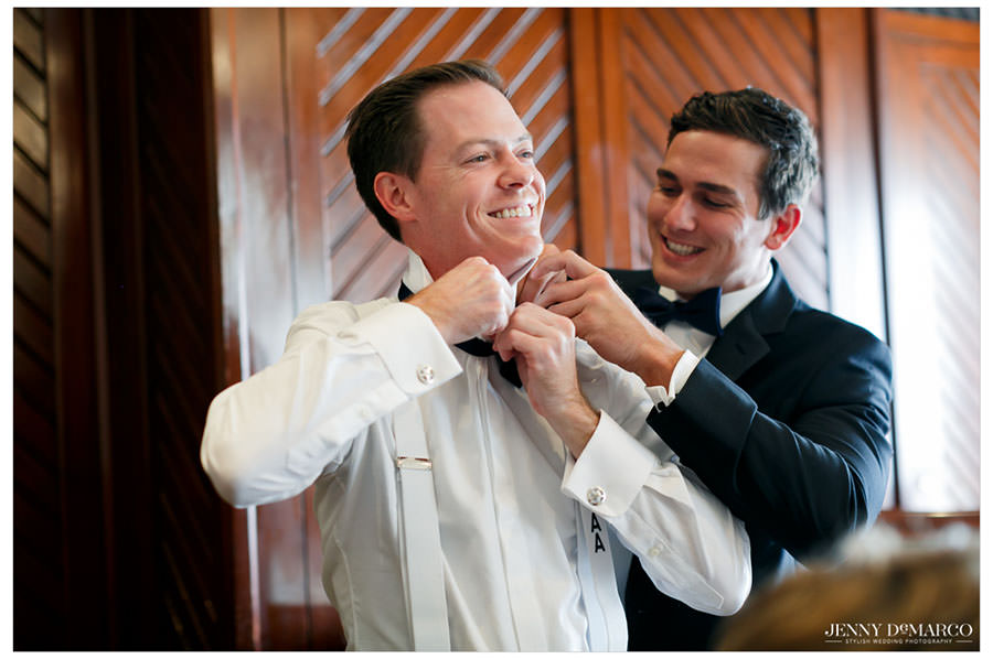 Groomsmen helping the groom put on his bow tie