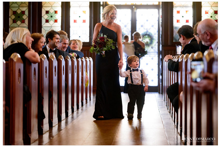 Bridesmaid walking the ring bearer down the aisle