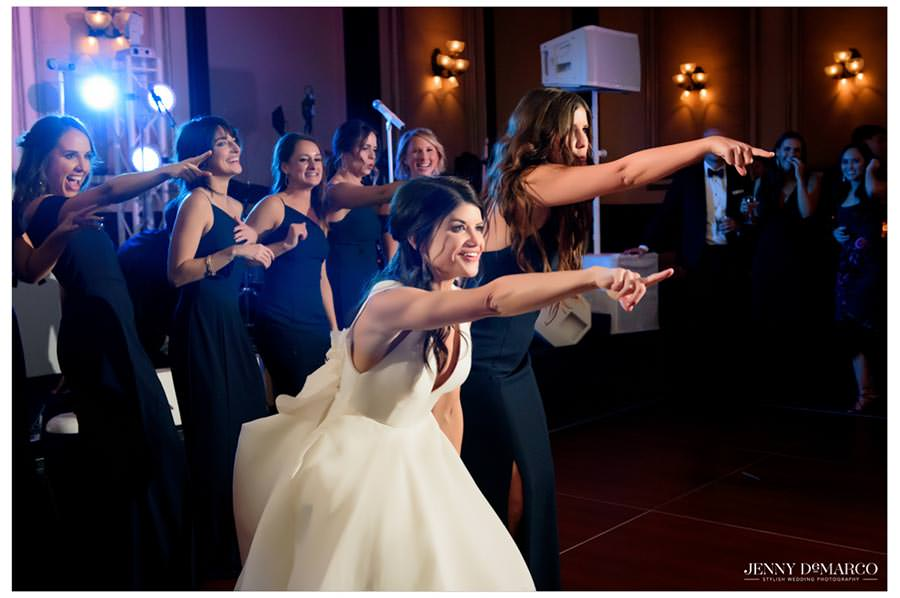 bride and bridesmaids dancing for the groom