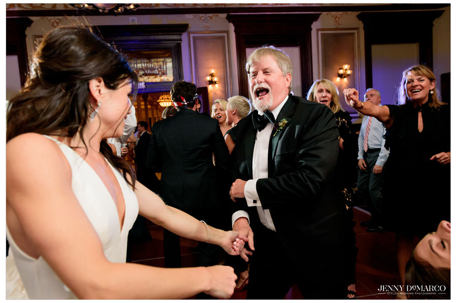 father of the bride and bride goofing off and dancing at the reception