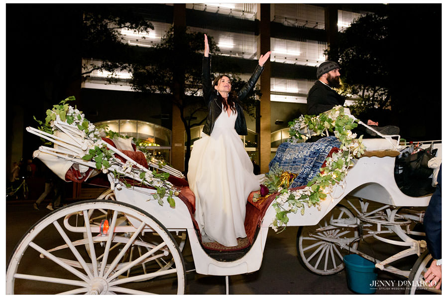 bride celebrating her wedding night by standing on a carriage