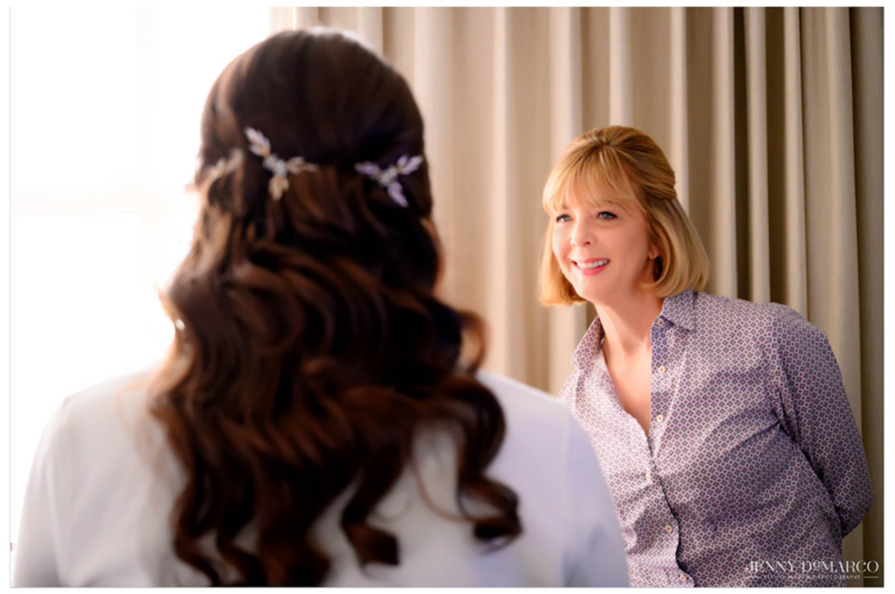 mom of bride watching as bride gets her makeup done