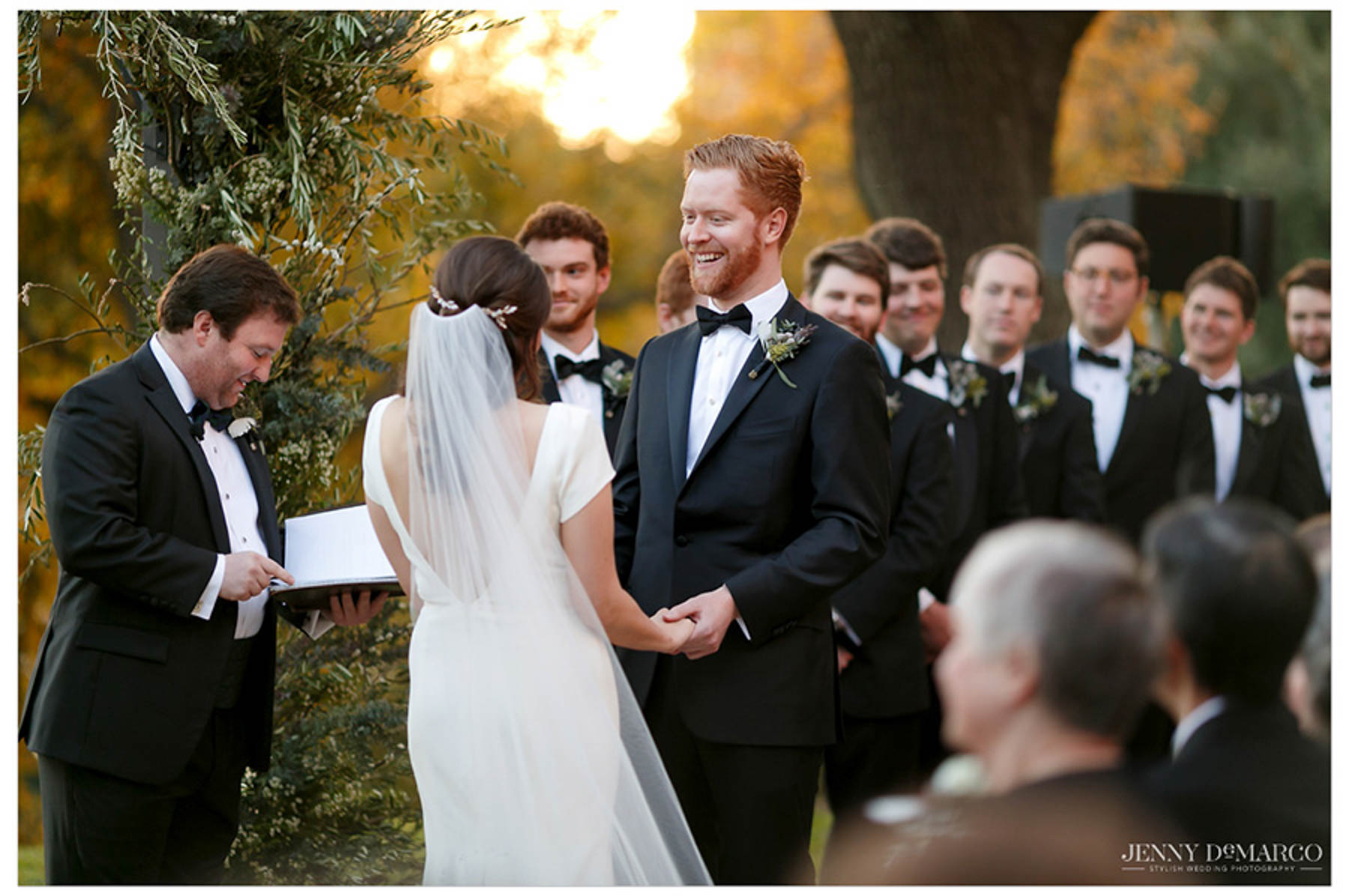 groom smiles at bride during ceremony