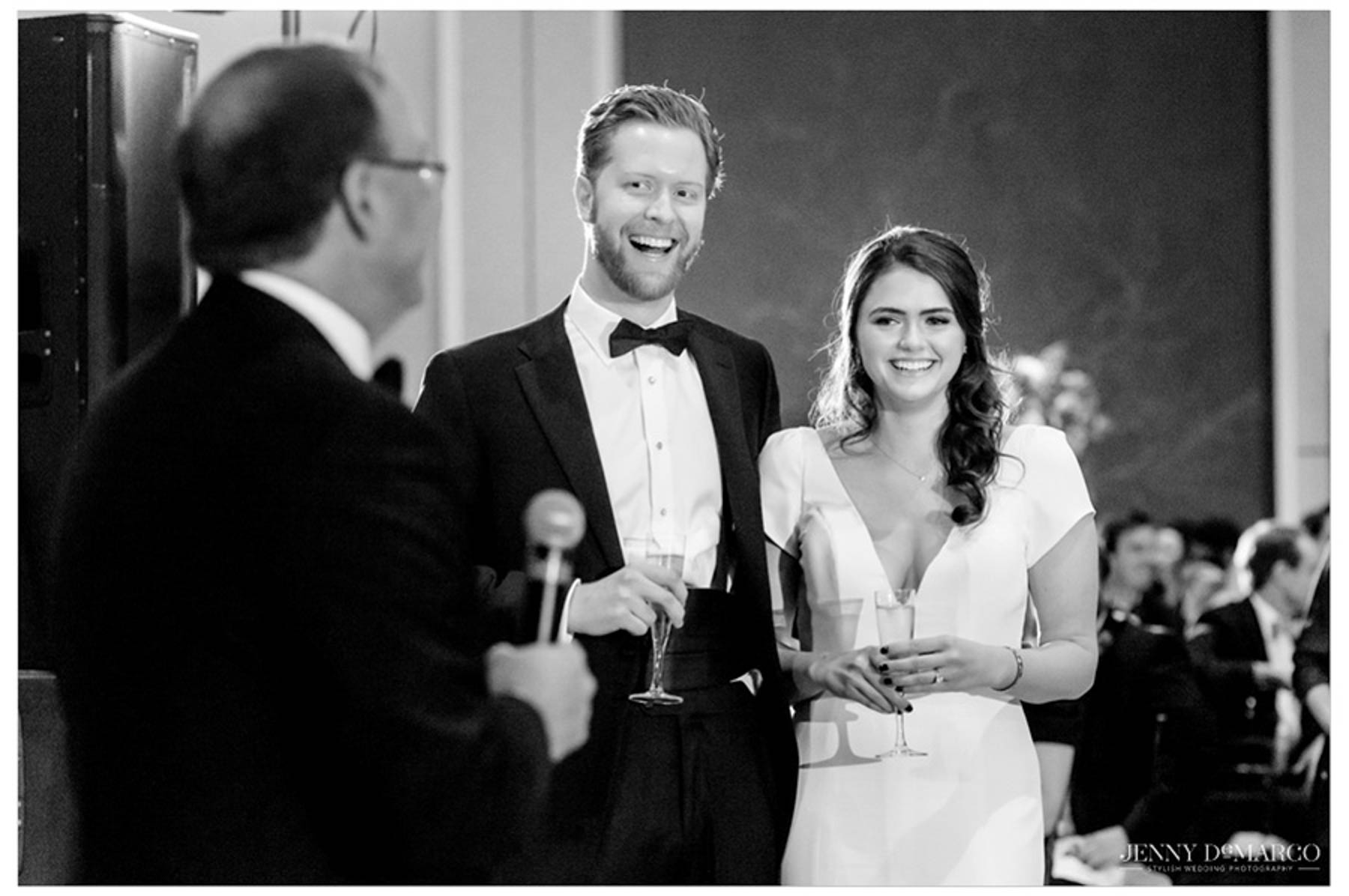 bride and groom smile as father makes his speech