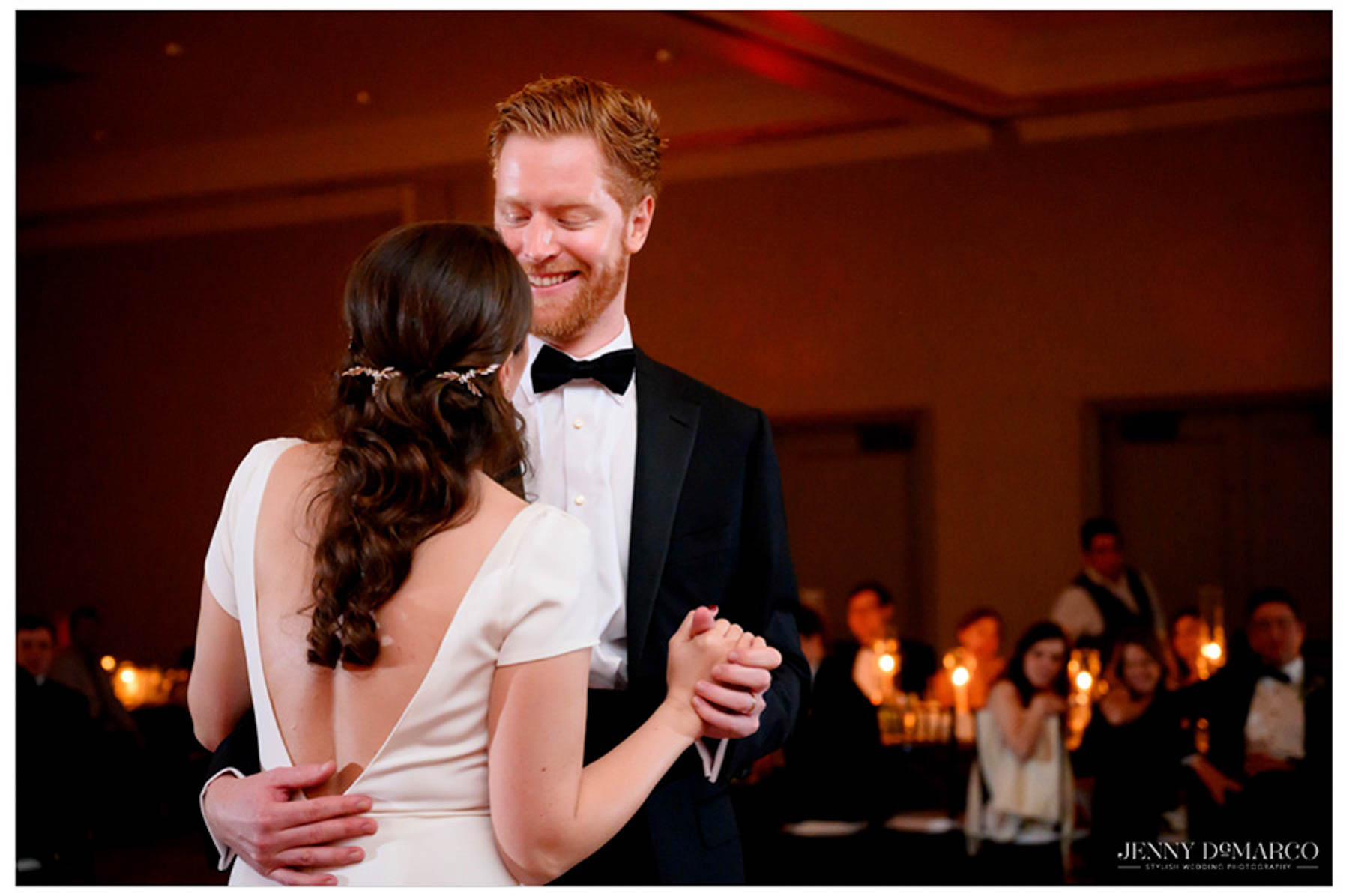groom smiles down at bride during the first dance