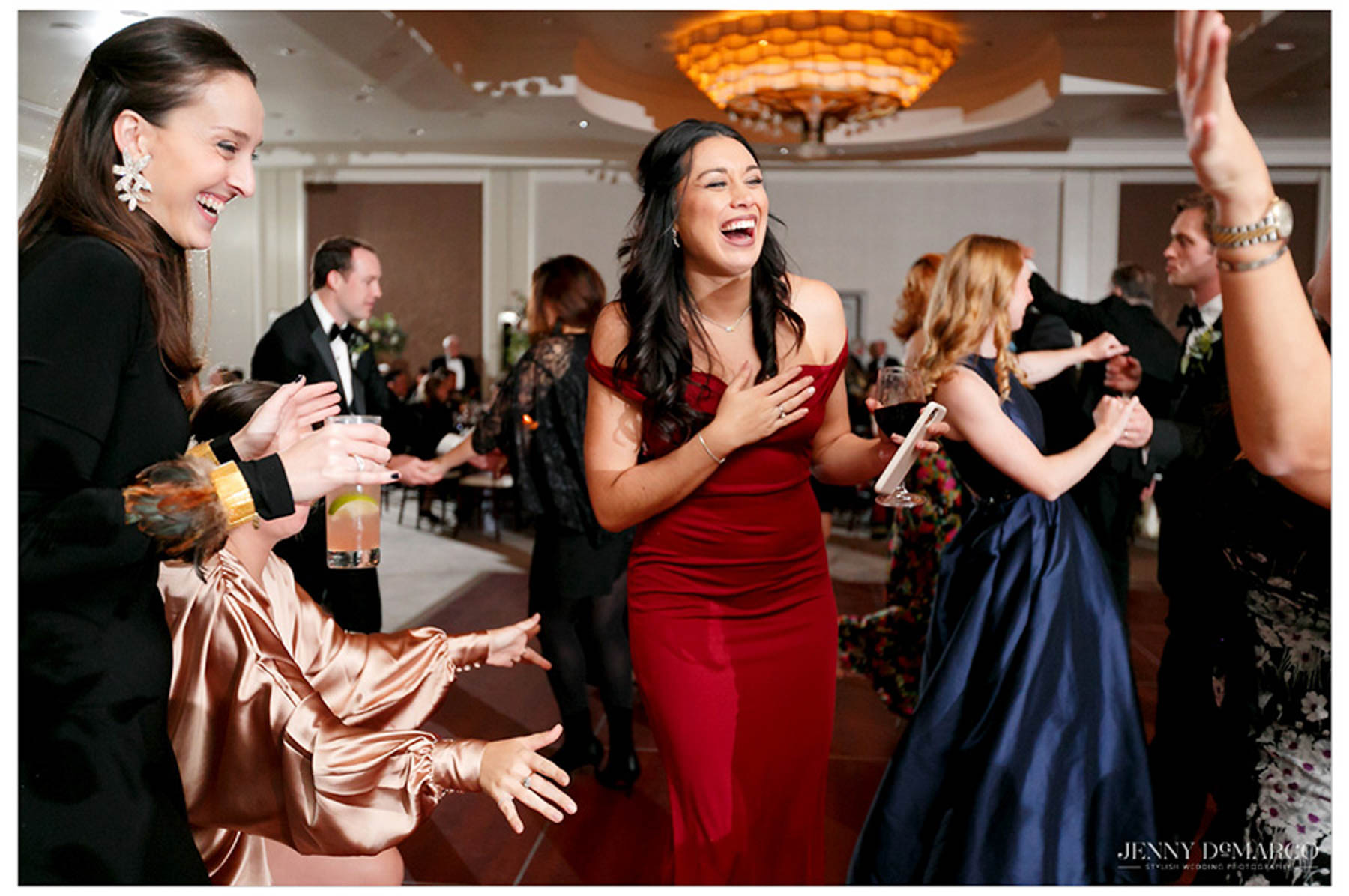 friend of couple dances in a red dress and laughs