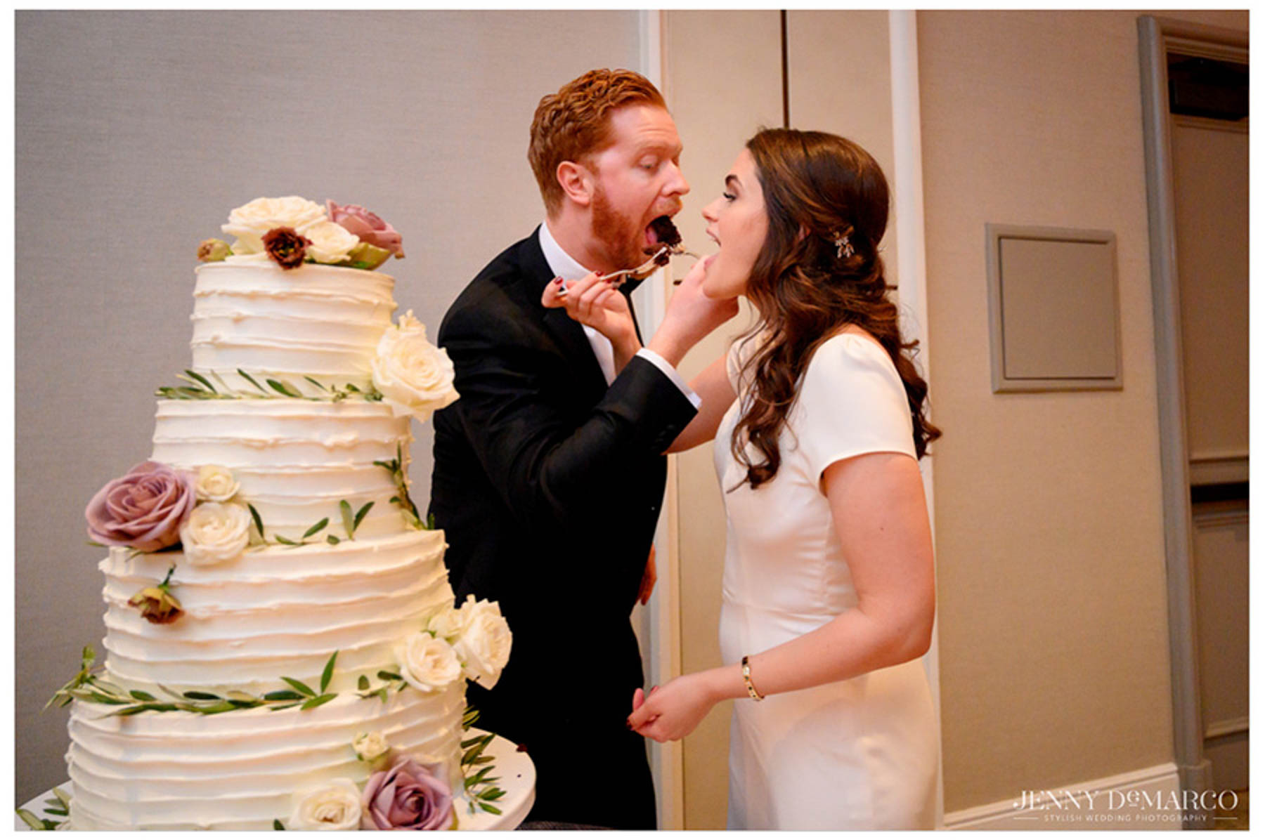 bride and groom feed each other the first bite of wedding cake