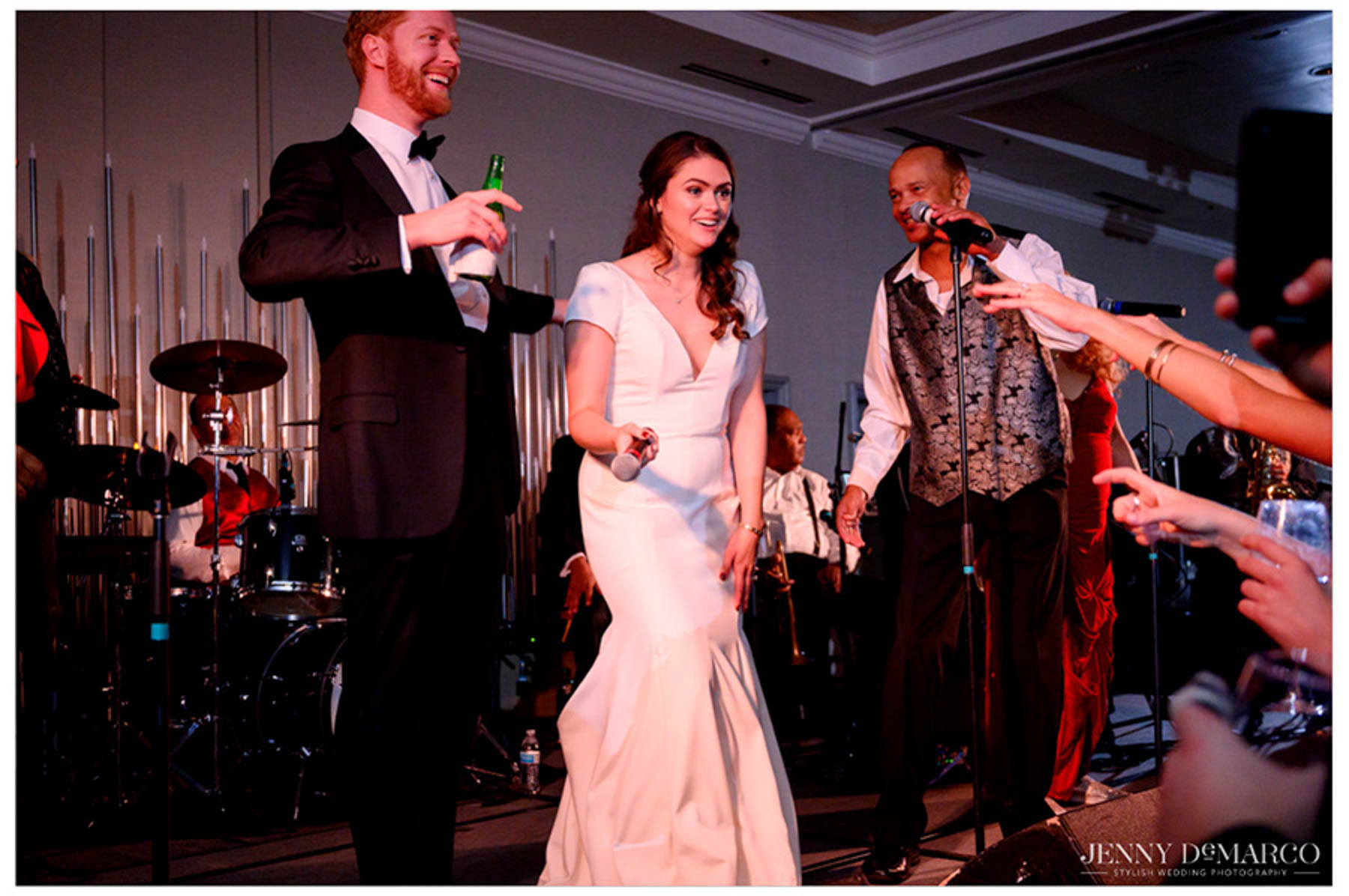 bride and groom laugh and sing on stage with the band