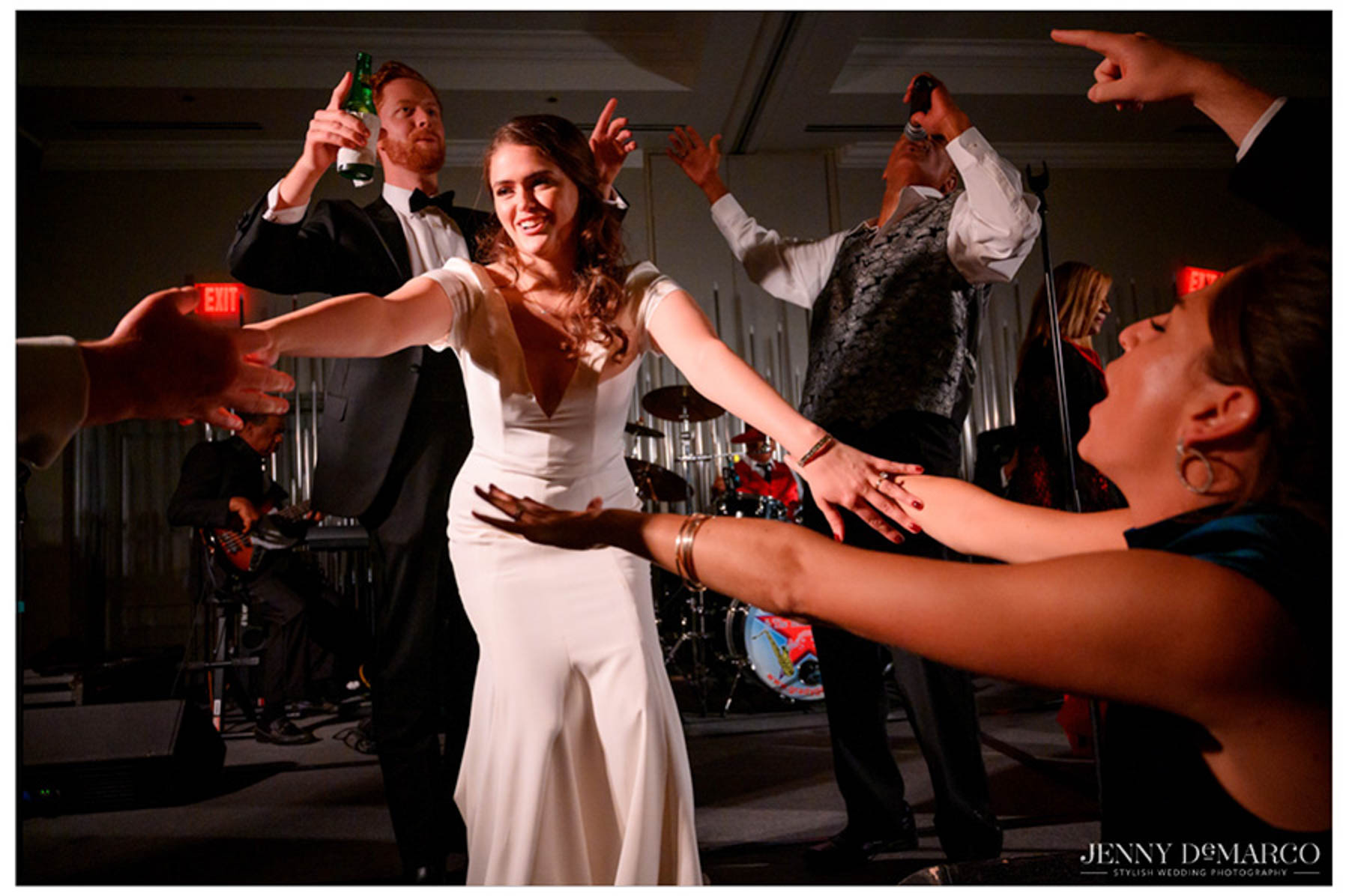 bride reaches for her friends and smiles on stage with the band