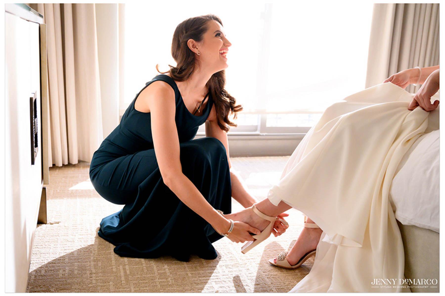 friend of bride puts shoe on bride