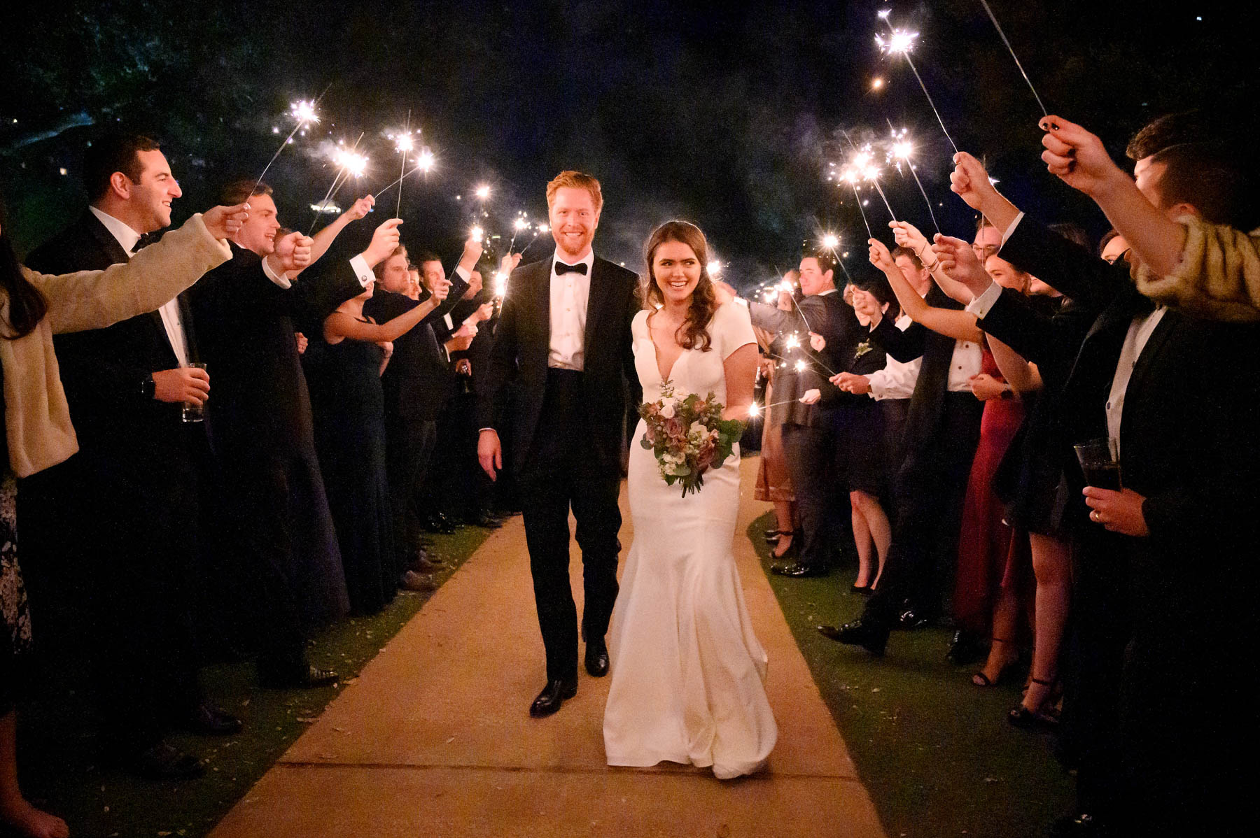 bride and groom walk out at the end of the night as guests hold up sparklers