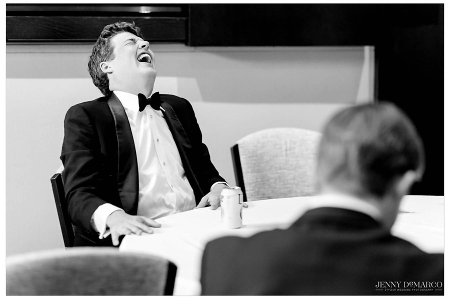 friend of groom laughs at a table as the boys get ready