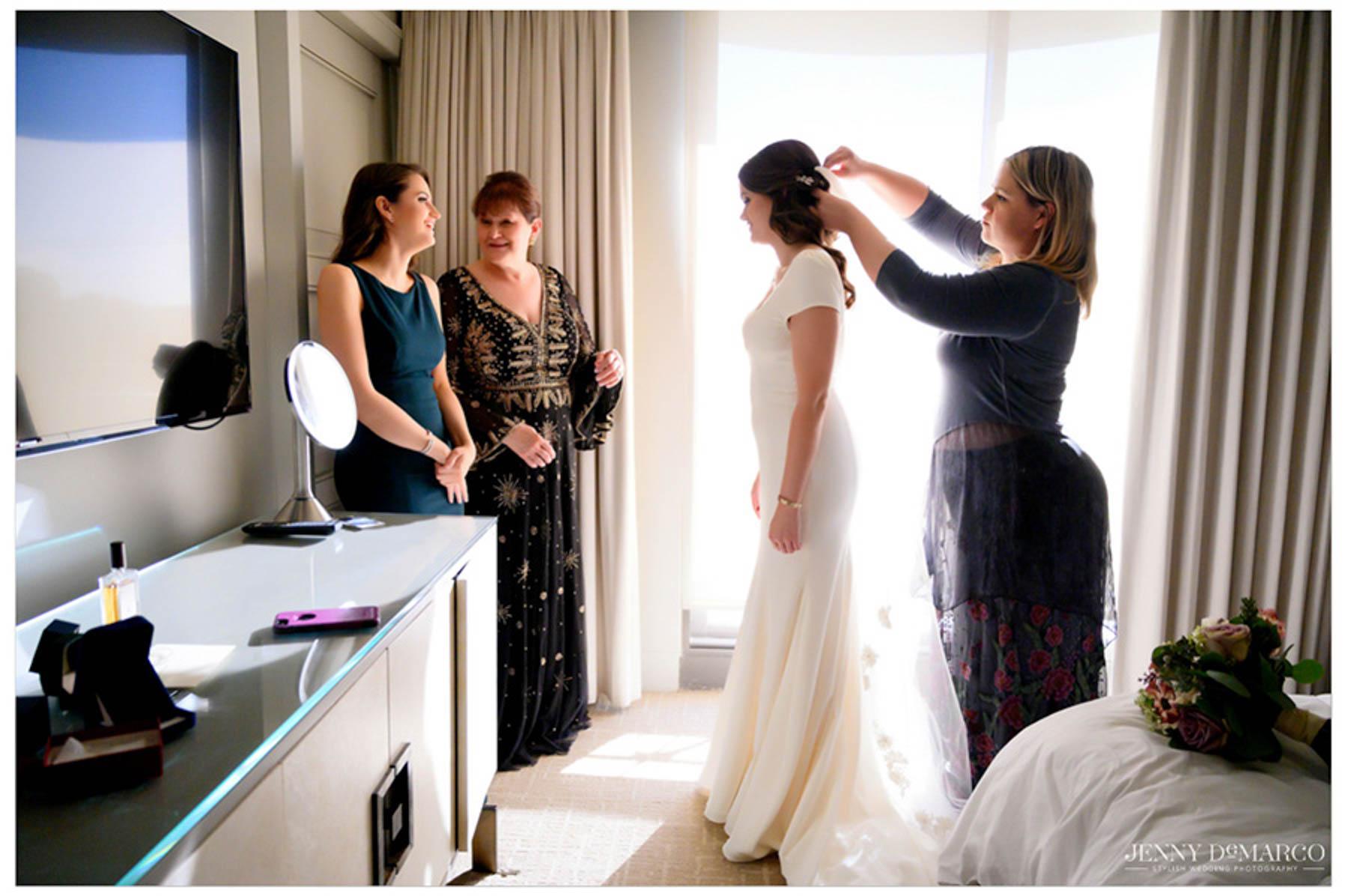 friend of bride puts veil in bride's hair