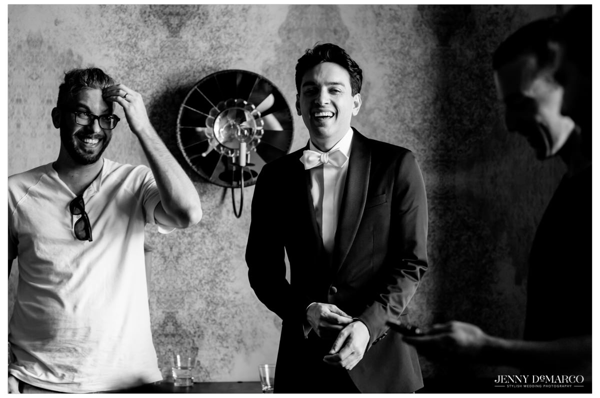 Groomsmen and groom laughing as they get ready for the wedding