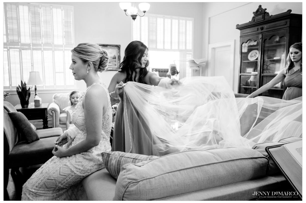 bridesmaids helping put the brides veil on