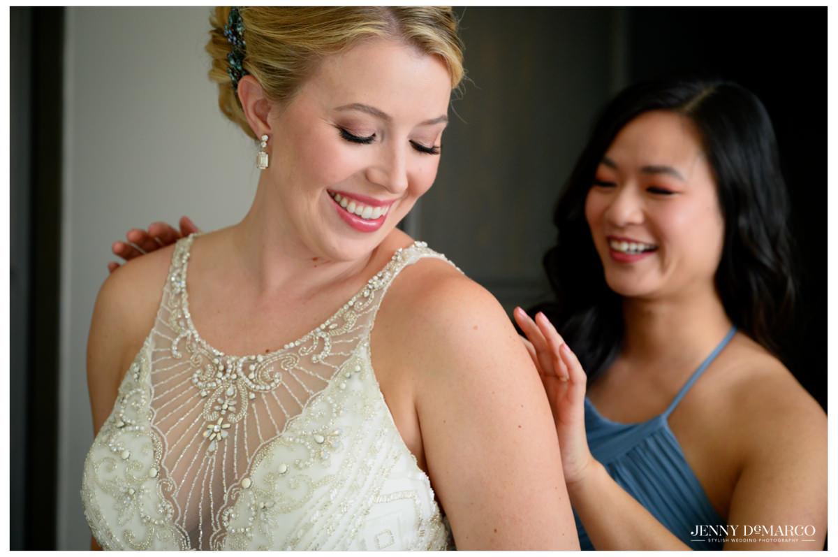 bridesmaid helping the bride put her wedding dress on