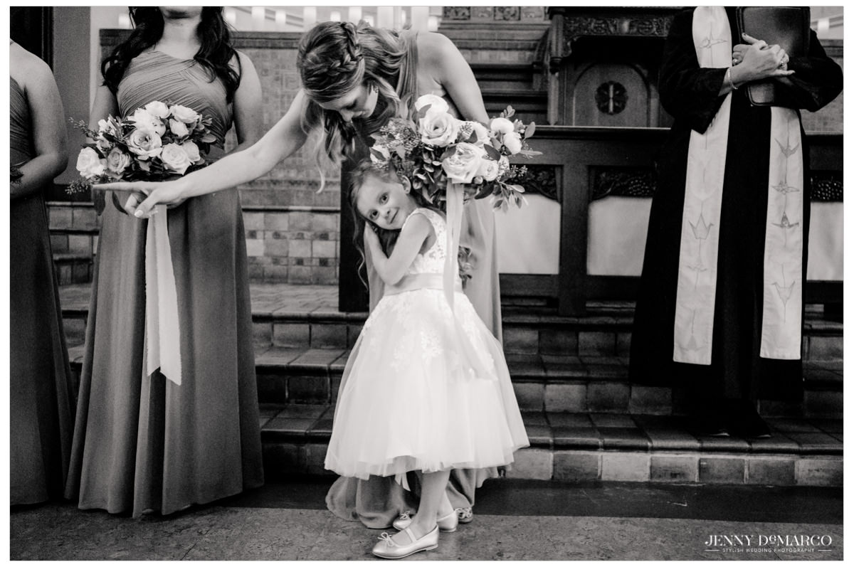 flower girl hugging on of the bridesmaids