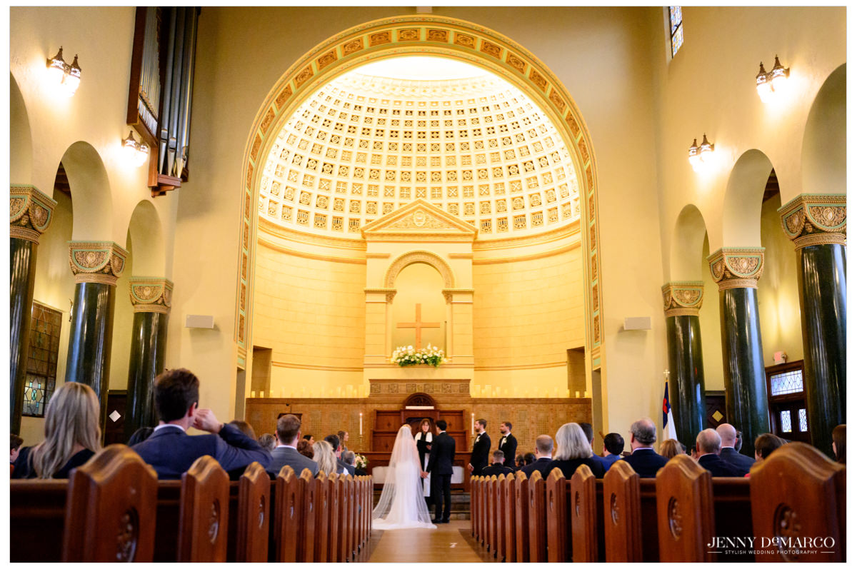 Wide shot of the inside of central christian church with the bride and groom at the altar