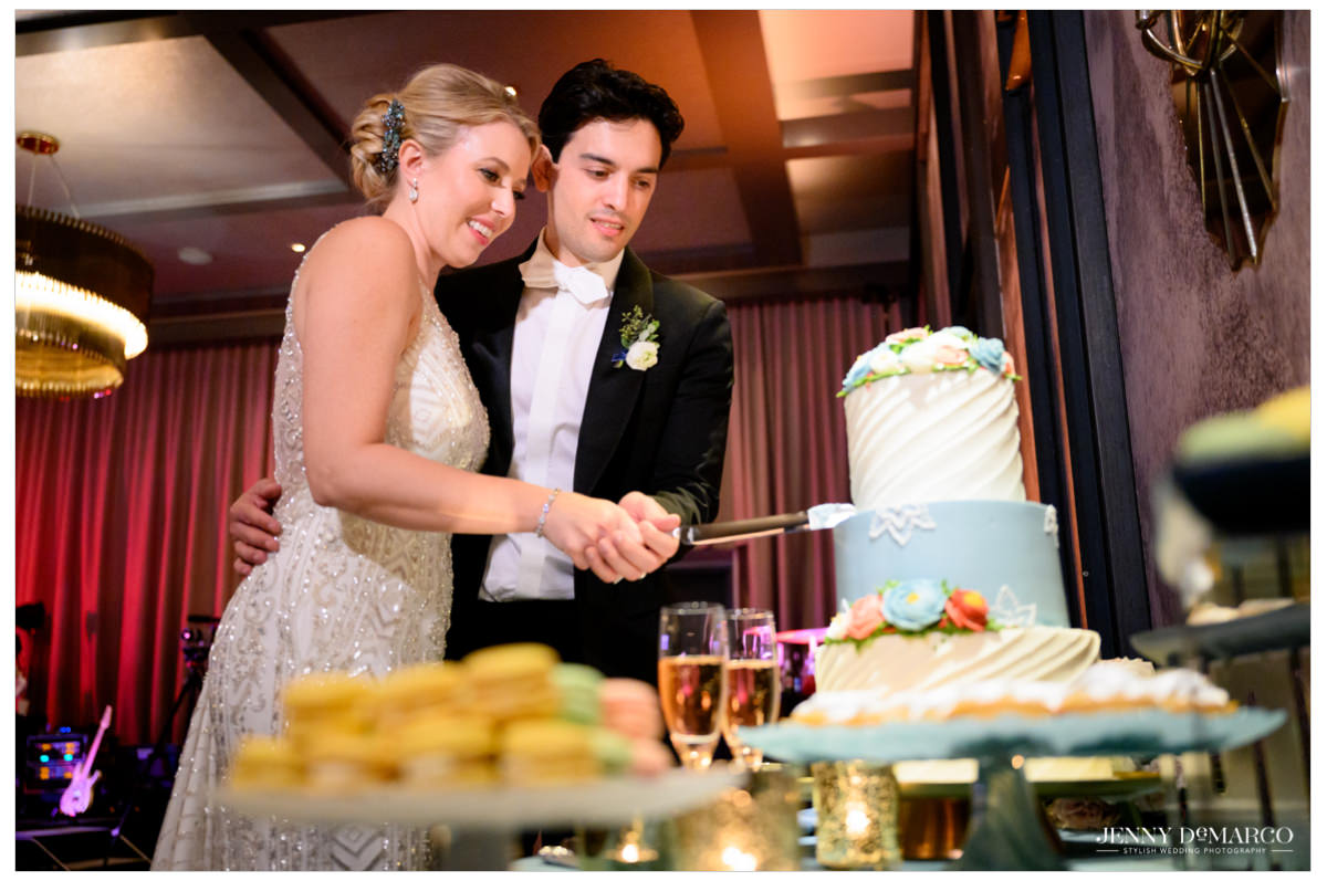 bride and groom cutting the white and light blue wedding cake